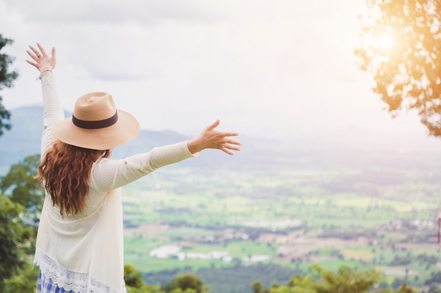 Voyageur de femme avec caméra tenant un chapeau et respirant au champ d'herbes et de forêt.