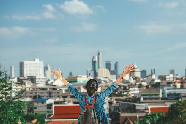 Voyageur de femme heureuse, levant les mains dans le fond de scène de ville avec espace de copie