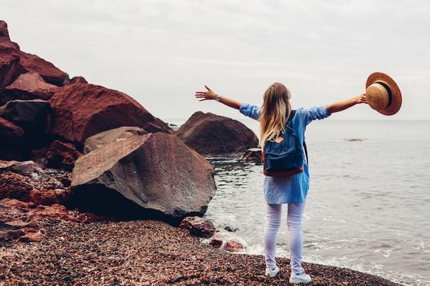 Voyageur femme marchant les bras levés se sentir heureux sur la plage rouge