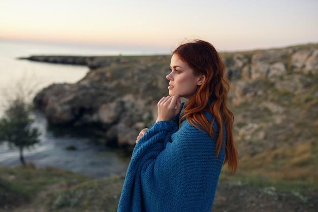 Voyageur de femme avec plaid bleu dans les montagnes dans la nature
