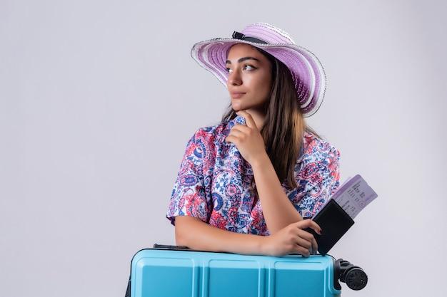 Voyageur femme portant chapeau d'été debout avec valise de voyage tenant des billets à côté avec la main près du menton pensant avoir des doutes sur blanc