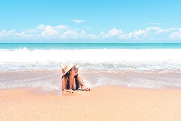 Voyageur femme portant un maillot de bain allongé sur la plage dans l'eau bleue tout en se relaxant en voyage de vacances