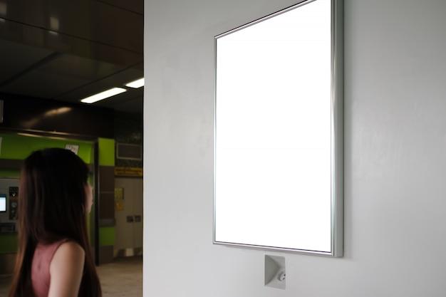 Voyageur femme regardant panneau publicitaire vide à la station de métro.
