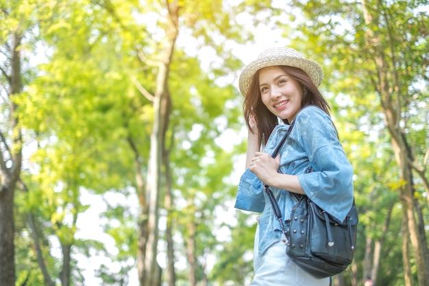 Voyageur de femme avec sac à dos, tenant un chapeau et en regardant la vue dans la forêt, concept de voyage