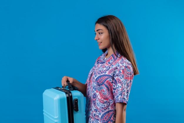 Voyageur femme tenant une valise de voyage à la confiance avec le sourire sur le visage debout sur le côté bleu isolé