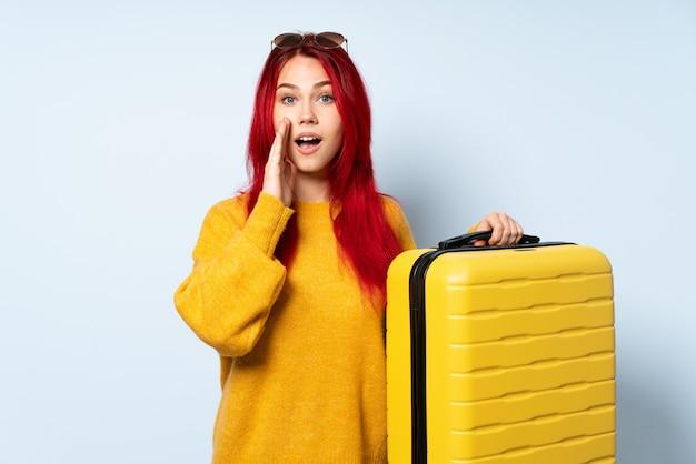 Voyageur, femme, tenue, valise, isolé, bleu, mur, surprise, choqué, expression faciale