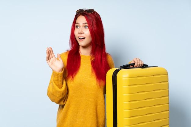 Voyageur, femme, tenue, valise, isolé, bleu, mur, surprise, expression faciale