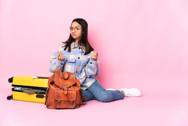 Voyageur femme avec une valise assis sur le sol en faisant un geste d'argent mais est ruiné