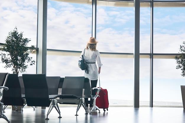 Voyageur de femme avec valise dans la salle d'attente de l'aéroport