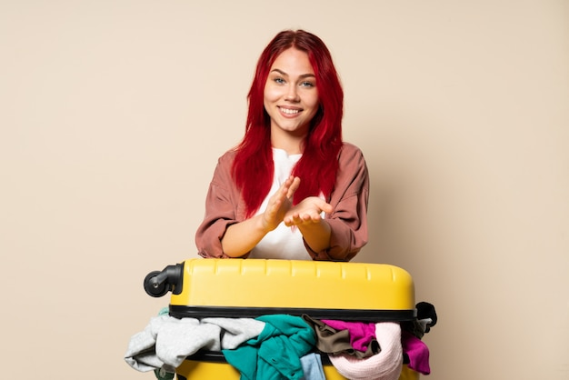 Voyageur femme avec une valise pleine de vêtements isolés sur le mur beige applaudissant après présentation lors d'une conférence