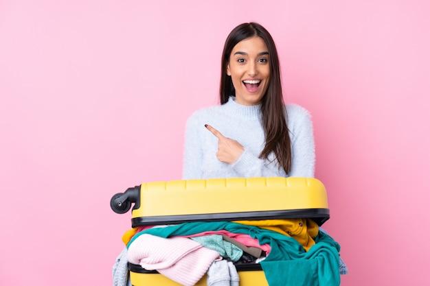Voyageur femme avec une valise pleine de vêtements sur le mur rose isolé pointant le doigt sur le côté