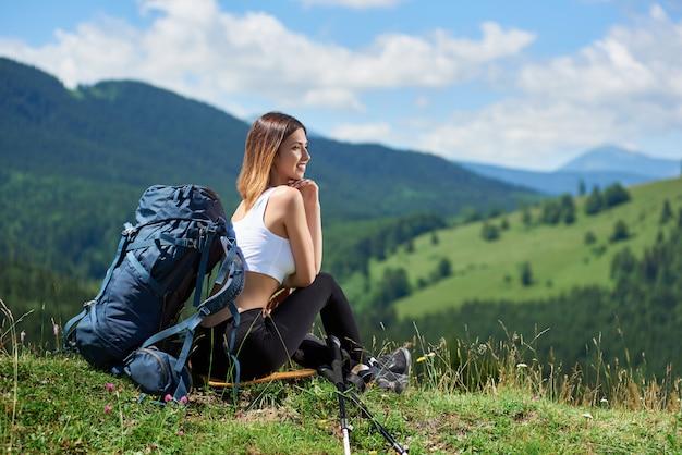 Voyageur de fille reposant au sommet d'une colline, en détournant les yeux, profitant de la journée d'été. montagnes, forêts et ciel nuageux sur l'arrière-plan flou