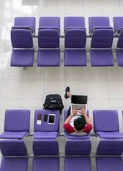 Voyageur heureux homme asiatique travaillant avec un ordinateur portable de la technologie