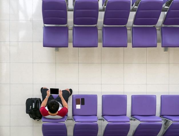 Voyageur heureux homme asiatique travaillant avec tablette de technologie avec valise