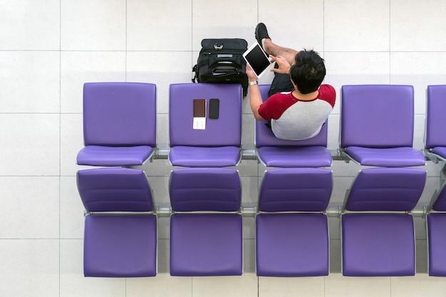 Voyageur heureux homme asiatique travaillant avec tablette de technologie