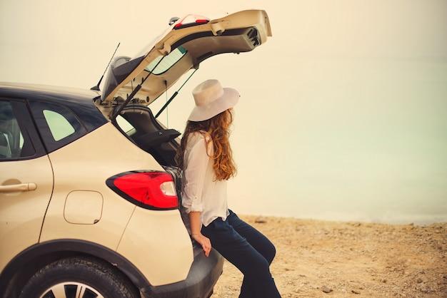 Voyageur heureux jeune femme élégante sur la route de la plage assis sur une voiture blanche multisegment