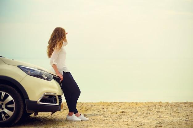 Voyageur heureux jeune femme élégante sur la route de la plage assis sur une voiture blanche multisegment.