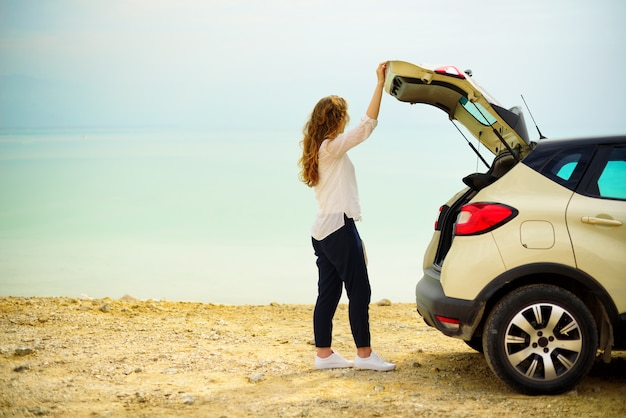 Voyageur heureux jeune femme élégante sur la route de la plage près de la voiture blanche crossover