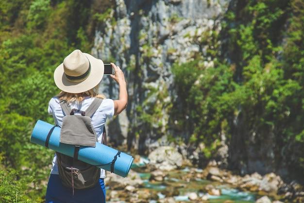 Voyageur hipster fille prend des photos de la nature sur le fond des montagnes voyageur touristique sur le fond.
