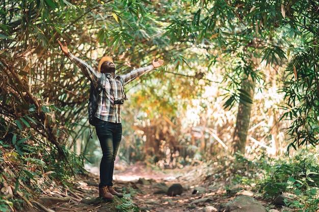 Voyageur d'homme africain de liberté tenant l'appareil photo avec sac à dos, debout dans la forêt naturelle verte.