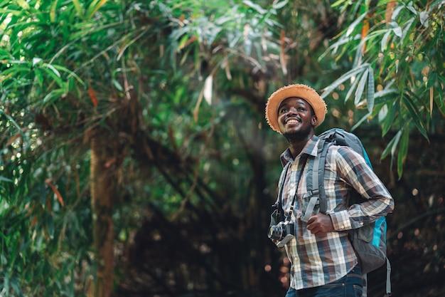 Voyageur homme africain tenant la caméra avec sac à dos debout dans la forêt naturelle verte.