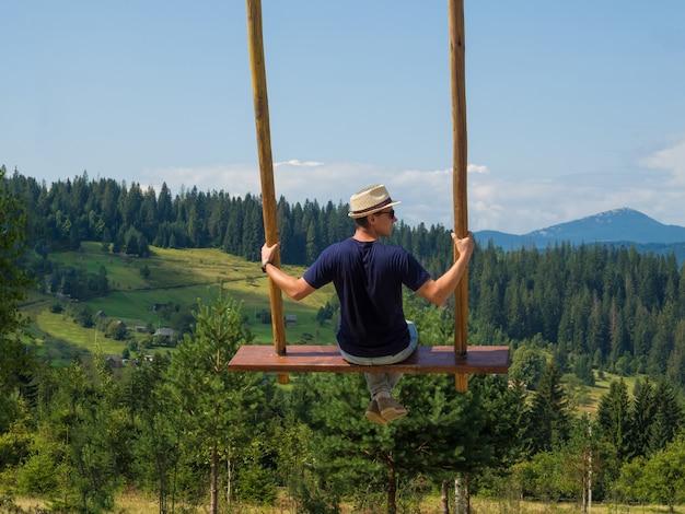 Voyageur homme appréciant de se balancer sur une balançoire céleste et une vue sur la montagne