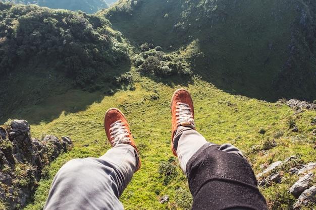 Voyageur de jambes se détendre et accroché sur la falaise avec la montagne à feuilles persistantes