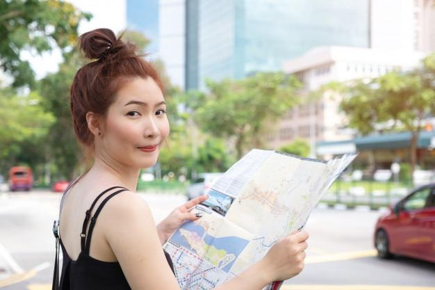 Voyageur de jeune femme asiatique tenant la carte à côté de la route à singapour