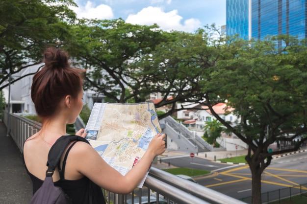 Voyageur de jeune femme asiatique tenant la carte pour trouver la direction à singapour