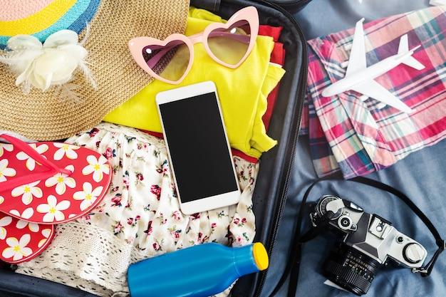 Voyageur de la jeune femme, emballant ses vêtements et des trucs dans la valise