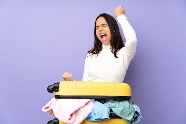 Voyageur jeune femme avec une valise pleine de vêtements isolés