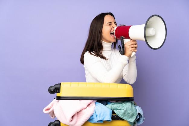 Voyageur jeune femme avec une valise pleine de vêtements sur le mur violet criant à travers un mégaphone