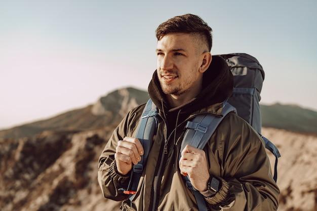 Voyageur jeune homme caucasien avec gros sac à dos randonnée dans les montagnes