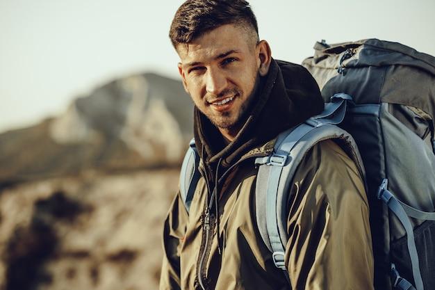 Voyageur jeune homme caucasien avec gros sac à dos de randonnée dans les montagnes