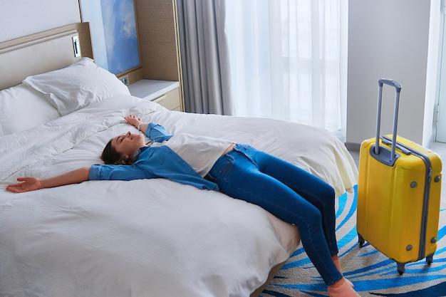 Voyageur joyeux satisfait femme allongée sur un lit dans la chambre de l'hôtel après l'enregistrement et début de voyage réjouissant