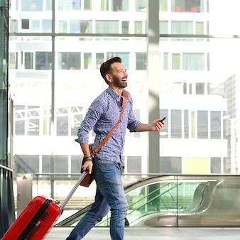 Voyageur mâle mature souriant, marchant avec valise et téléphone portable
