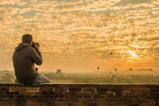 Voyageur mâle photographiant des temples à bagan myanmar au lever du soleil
