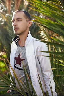 Voyageur masculin dans le portrait d'oasis de forêt tropicale à l'arrière-plan des feuilles de palmiers, mec non rasé parmi la végétation tropicale. une oasis dans le désert du maroc. découvrez l'inconnu dans la jungle
