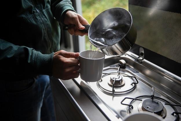 Voyageur masculin faisant son café dans une camionnette