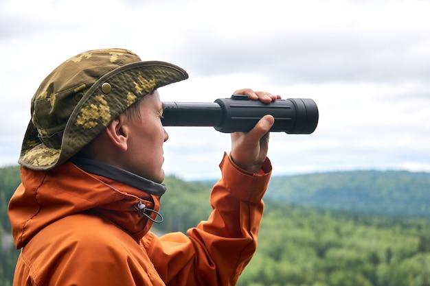 Le voyageur masculin regarde au loin dans un télescope contre le paysage naturel