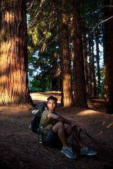 Voyageur masculin relaxant dans la forêt