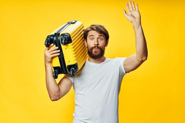 Voyageur masculin avec une valise dans ses mains posant, vacances