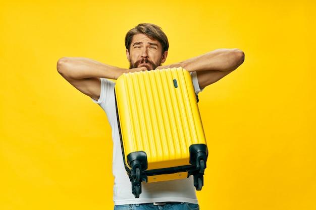 Voyageur masculin avec une valise dans ses mains posant des vacances