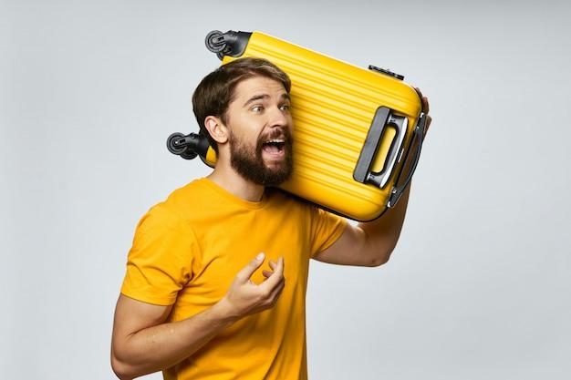 Voyageur masculin avec une valise dans ses mains posant