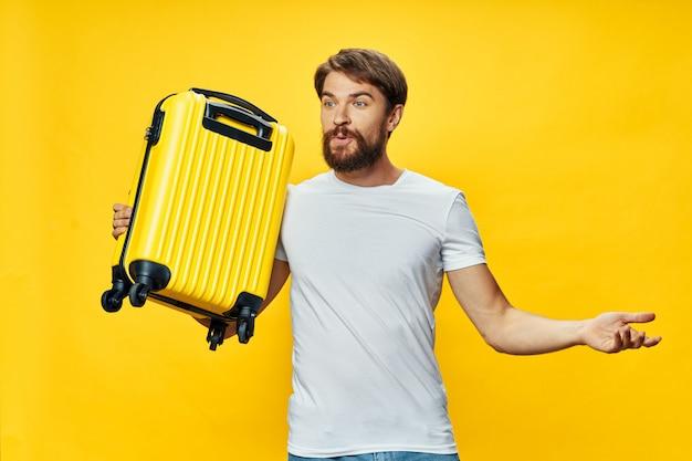 Voyageur masculin avec une valise dans ses mains qui pose en studio, vacances