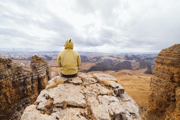 Un voyageur masculin en veste est assis au bord d'une falaise et profite de la nature montagnarde