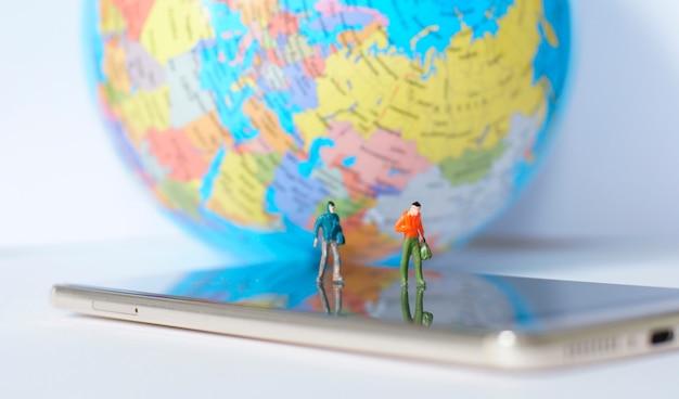 Voyageur miniature marchant sur la carte du monde