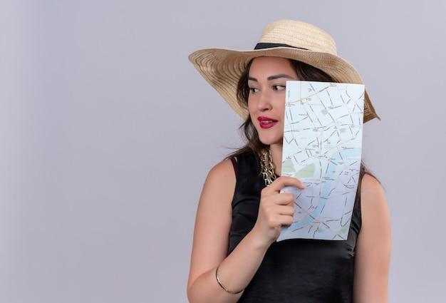 Voyageur de la pensée jeune fille portant un maillot de corps noir en chapeau tenant une carte sur fond blanc
