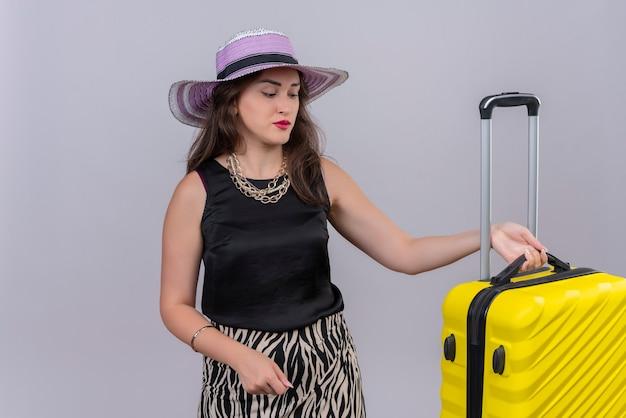 Voyageur de la pensée jeune fille portant un maillot de corps noir en chapeau tenant valise sur fond blanc