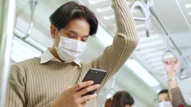 Voyageur portant un masque tout en utilisant un téléphone mobile dans un train public